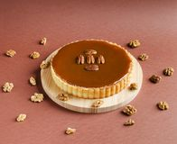 Caramel nuts tartlet with pecan nuts on wood board Stock Photography