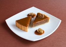 Caramel nuts tartlet pieces on white plate Royalty Free Stock Photography