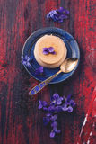 Caramel pannacotta with violet flowers Royalty Free Stock Photo