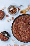 Caramel pecan pie. Homemade Big round caramel pecan pie and small tartlets in black iron forms, served with brown sugar, caramel sauce and vintage cutlery over Royalty Free Stock Photos