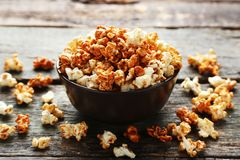 Caramel popcorn. In bowl on wooden table stock photo