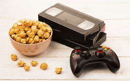 Caramel popcorn near a videotape and gamepad Stock Images