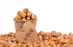 Caramel popcorn in a paper bucket. A pile of caramel creamy popcorn on a white background. royalty free stock photography