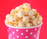 Caramel popcorn in paper cup. On red background Royalty Free Stock Photo