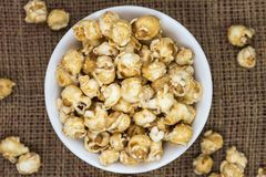 Caramel popcorn in white bowl on gunny sack. Sweet popcorn close-up on gunny sack background, top view Stock Images
