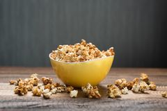 Caramel popcorn in a yellow bowl on a wooden table background royalty free stock image