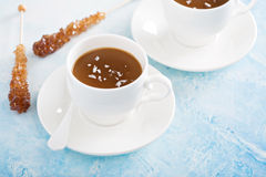 Caramel pudding with flaked salt. Caramel pudding in white cups with flaked salt Stock Photo