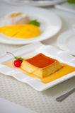 Caramel pudding on a white plate. Caramel pudding and melted sugar decoration on white plate Stock Photos