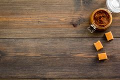 Caramel sauce in glass jar near caramel cubes on dark wooden background top view copy space Royalty Free Stock Image