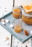 Caramel sauce. Jar of homemade caramel sauce, served with sugar cubes over wooden table stock images