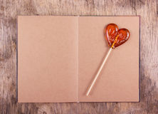 Caramel on a stick in the shape of a heart and an old diary with blank pages. Stock Image