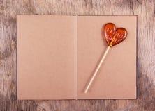 Caramel sur un bâton sous forme de coeur et un vieux journal intime avec les pages vides Image stock