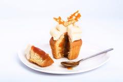 Caramel sweet cupcake cut on a white background. Stock Image