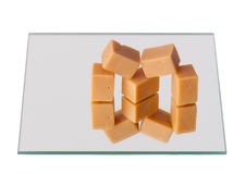 Caramel sweets on a mirror, isolated Stock Images