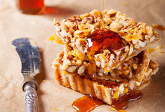 Caramel tart with nuts, maple syrup and honey. Caramel tart with nuts, maple syrup and honey on a wooden background stock photography
