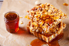 Caramel tart with nuts, maple syrup and honey. Caramel tart with nuts, maple syrup and honey on a wooden background royalty free stock image