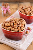 Caramelized almond with cinnamon in shart shaped red bowls Royalty Free Stock Images