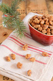 Caramelized almonds and Christmas tree twigs. Decoration with roasted sugared almonds in red heart shaped bowl and Christmas tree twigs on wooden background stock photo