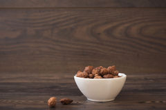 Caramelized almonds in a small white bowl on a wood background Royalty Free Stock Image