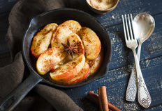 Caramelized apples with cinnamon and anise in scourage. On a dark wooden background Stock Photography