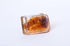 Caramelized cane sugar cube on white Royalty Free Stock Photos