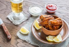 Caramelized chicken wings with glass of beer Stock Images