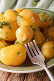 Caramelized new potatoes with herbs close-up on a plate. Vertica Stock Image