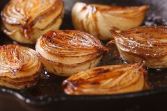 Caramelized onion halves with balsamic vinegar in a pan. Close-up, horizontal royalty free stock photos