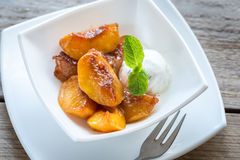 Caramelized peaches with vanilla ice cream Royalty Free Stock Images