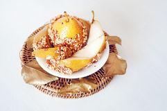 Caramelized pear dipped with peanuts decorated with golden leave Stock Images