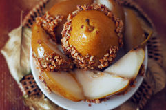 Caramelized pear dipped with peanuts decorated with golden leave Stock Photos