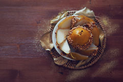 Caramelized pear dipped with peanuts decorated with golden leave Stock Photo