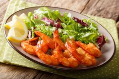 Caramelized prawns with honey and soy sauce and fresh lettuce cl. Ose-up on a plate on the table. horizontal stock photography