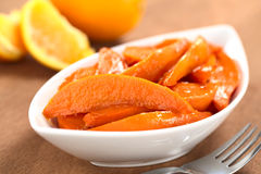 Caramelized Sweet Potato Wedges. Bowl of sweet potato wedges caramelized with brown sugar and fresh orange juice with a fork on the side and oranges in the back royalty free stock images