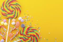 Caramella della lecca-lecca dell'arcobaleno sulla tavola di legno gialla luminosa Fotografie Stock