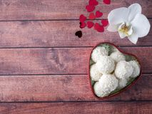 Caramella della noce di cocco in uno spazio di legno della copia del fondo del cuore del fiore rosso dell'orchidea Fotografia Stock