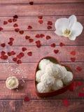 Caramella della noce di cocco in uno spazio di legno della copia del fondo del cuore del fiore rosso dell'orchidea Immagine Stock Libera da Diritti