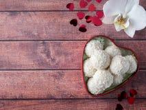 Caramella della noce di cocco in uno spazio di legno della copia del fondo del cuore del fiore rosso dell'orchidea Immagini Stock Libere da Diritti