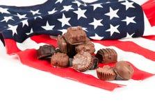 Caramella di cioccolato sulla bandiera americana Fotografia Stock