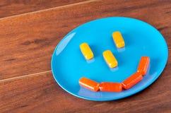 Caramella dura rettangolare variopinta disposta come fronte sorridente sul piatto blu con fondo di superficie di legno Fotografia Stock
