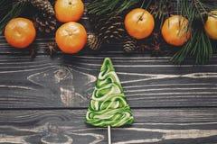 Caramella e mandarini dell'albero di Natale con i rami verdi dell'abete con Fotografia Stock Libera da Diritti
