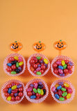 Caramella felice di scherzetto o dolcetto di Halloween su fondo arancio moderno variopinto luminoso Immagine Stock