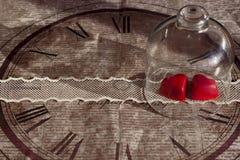 Caramella in forma di cuore rossa in un caso di vetro su un nastro del pizzo su un fondo di vecchia carta decorativa Immagine Stock
