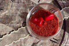 Caramella in forma di cuore rossa in un caso di vetro su un nastro del pizzo su un fondo di vecchia carta decorativa Fotografie Stock