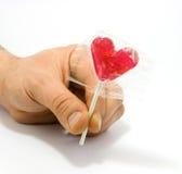Caramella a forma di della mano del cuore umano della holding Immagine Stock