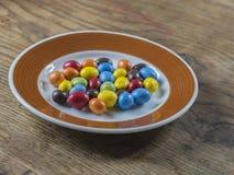 Caramella variopinta del bonbon sul piatto marrone bianco sullo scrittorio di legno Fotografia Stock