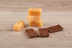Caramelle del caramello e pezzi di cioccolato sul fondo di legno della tavola Fotografia Stock