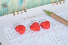 Caramelle del cuore ricoperte di zucchero sul calendario Immagine Stock