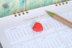 Caramelle del cuore ricoperte di zucchero sul calendario Fotografia Stock