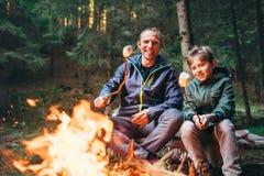 Caramelle della caramella gommosa e molle dell'arrosto del figlio e del padre su fuoco di accampamento in foresta immagine stock